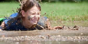 A big splash envelopes a girls face as she fall into a mud puddle